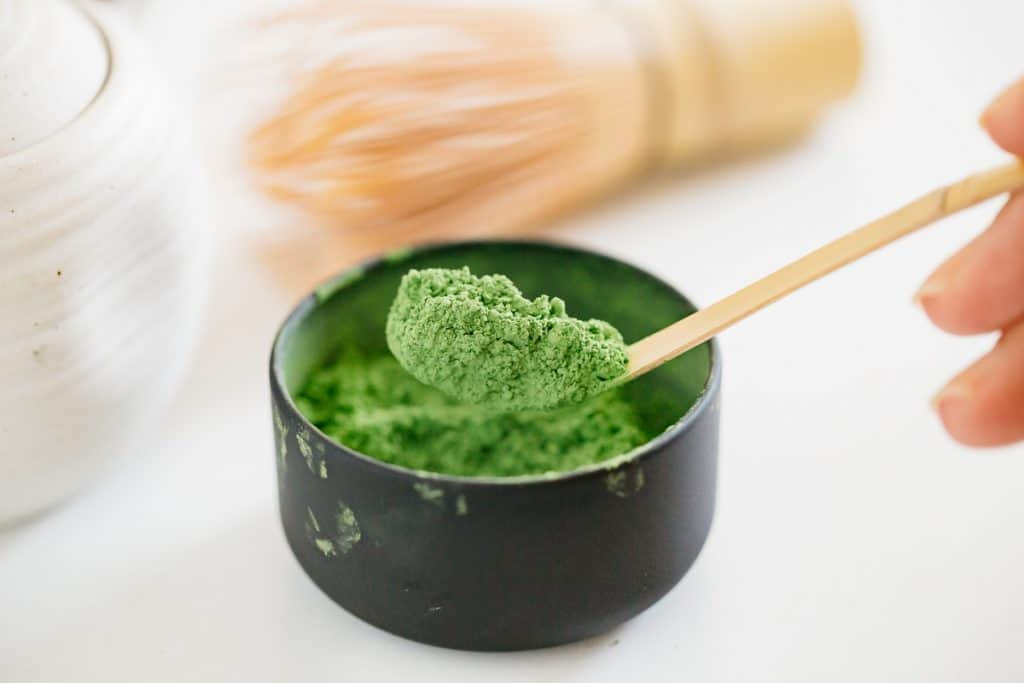 vivid green coloured matcha green tea powder scooped out with a little bamboo tea spoon
