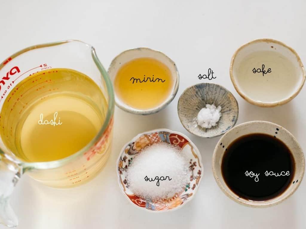 dashi stock in a jag mirin, salt, sake, soy sauce and sugar in small bowls
