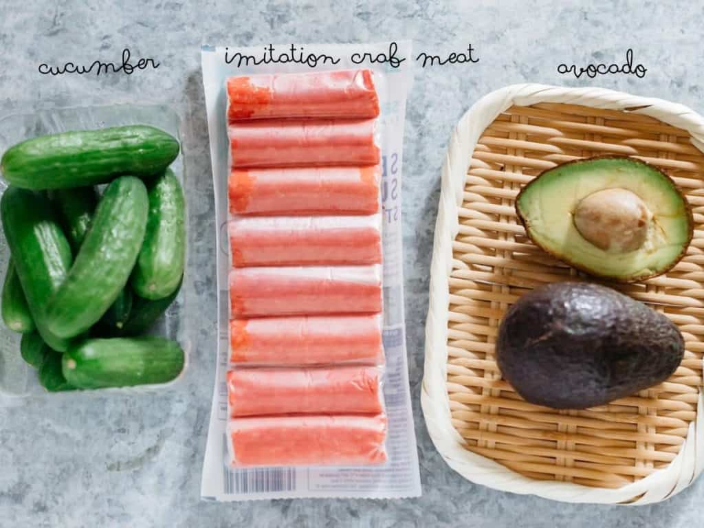 Cucumbers, a packet of imitation crab meat, and avocado cut in halves