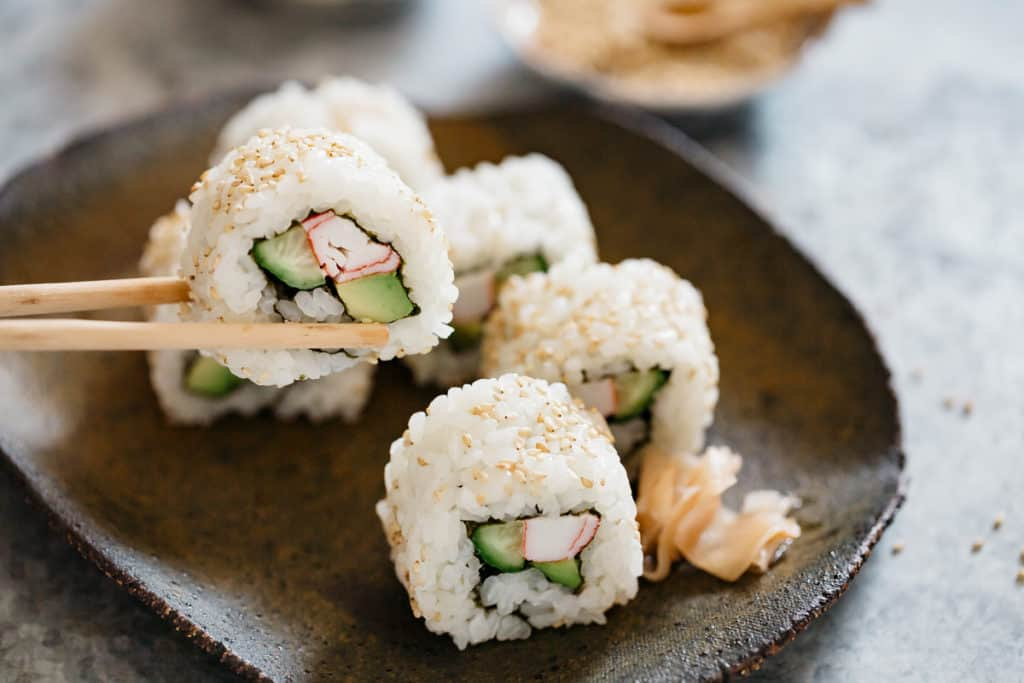A pair of chopstick is picking up a piece of California Roll from a plate of California rolls