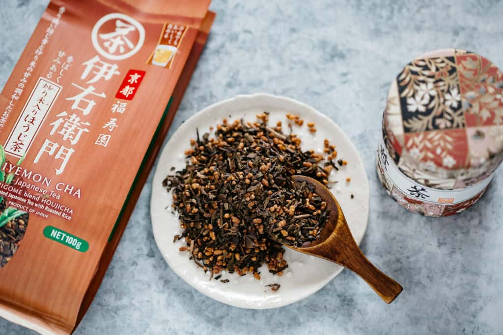 Hojicha leaves on a round plate with a wooden table spoon and packaging on both side
