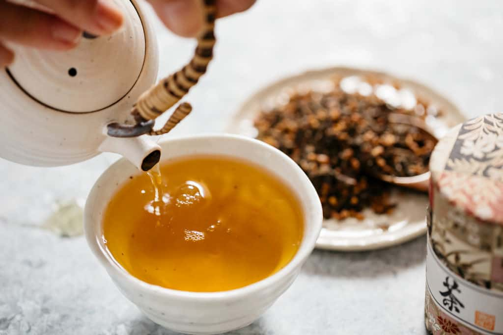 Hojicha poured into a small bowl from a Japanese tea pot