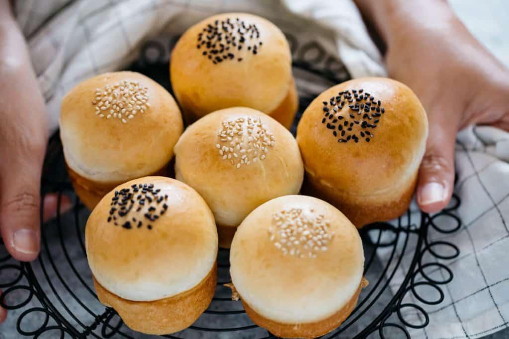 White bean paste bread and 3 azuki bean paste breads on a black wire rack