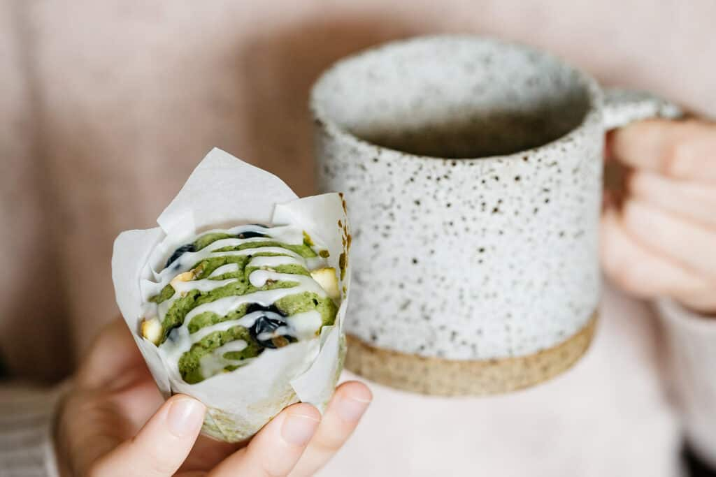 a hand holding matcha in one hand and a mug in another