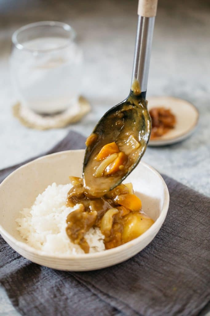 Japanese curry poring over a bowl of rice