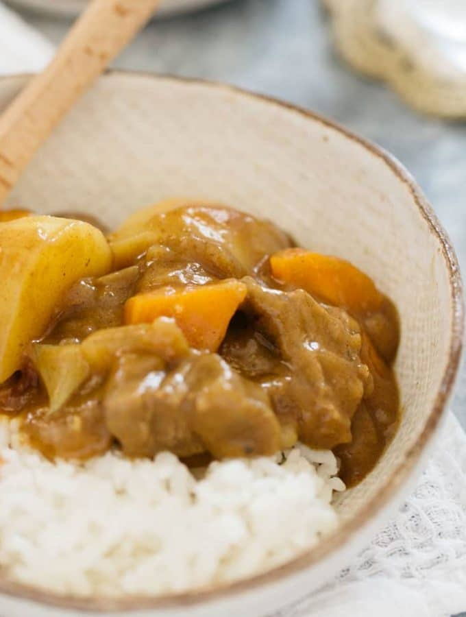 Japanese curry rice served in a Japanese pottery bowl with a small wooden spoon