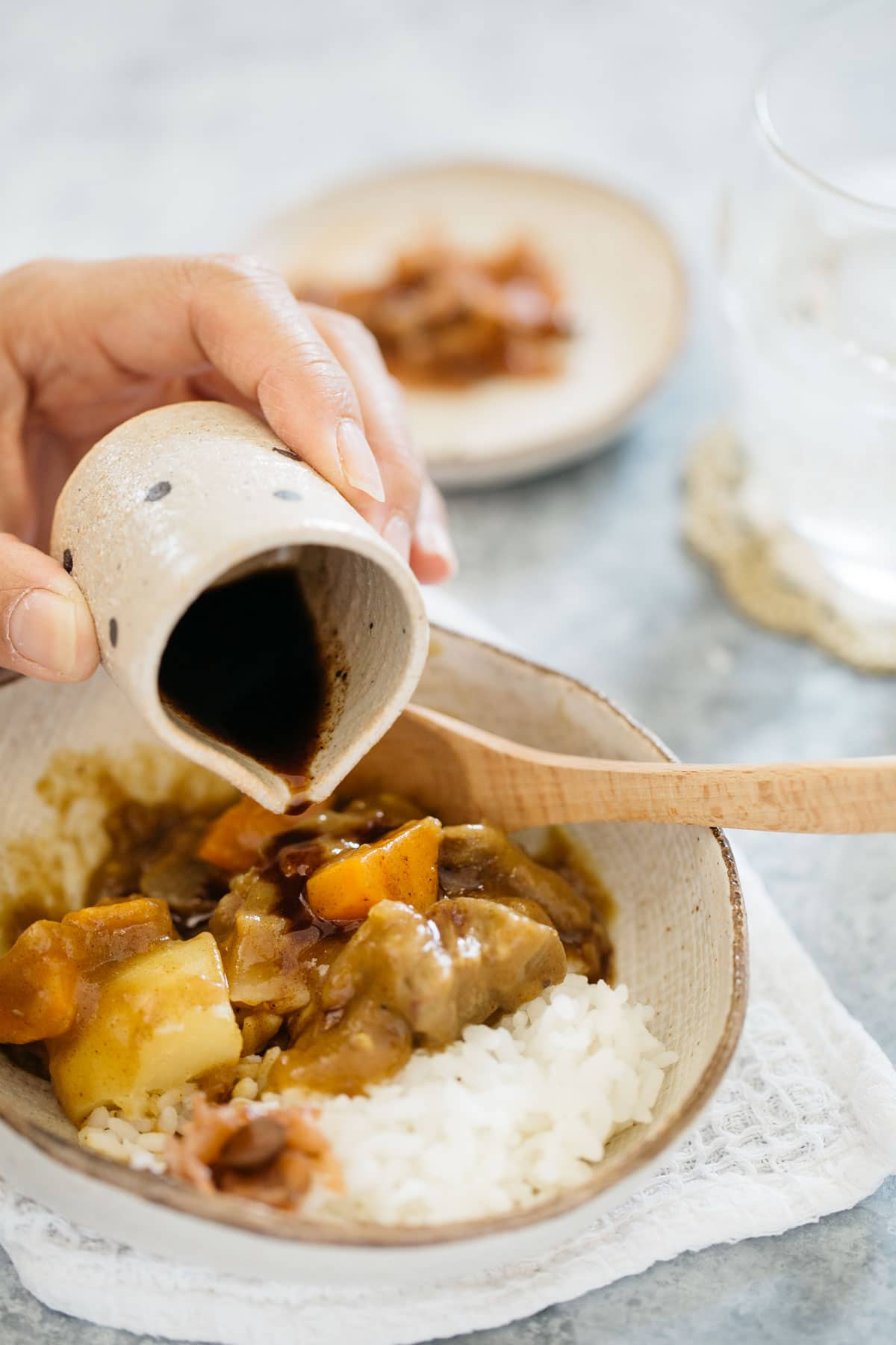 pouring worcestershire sauce over Japanese curry rice