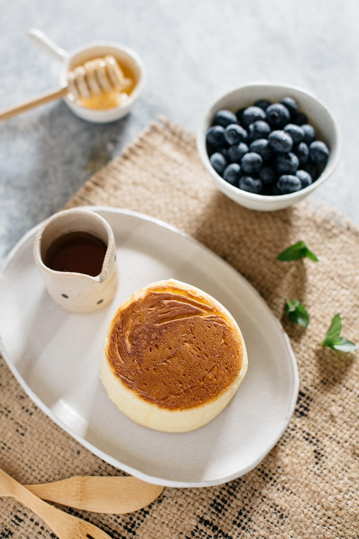 a bird view of Japanese pan cake with syrup and a bowl of blueberries