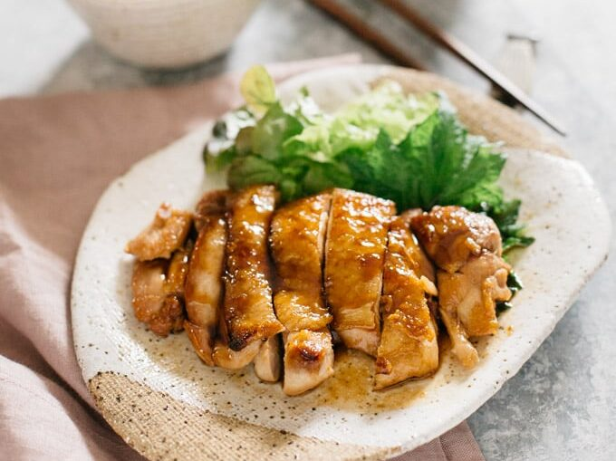 Teriyaki chicken served on a plate with shredded cabbage. Mirin made chicken glossy