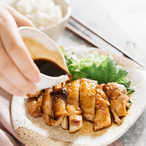 Teriyaki sauce poured over Teriyaki Chicken on the oval plate