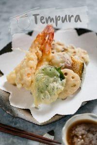 two prawn, shiso leaf, renkon, kabocha slice and chikuwa fish cake tempura on a plate
