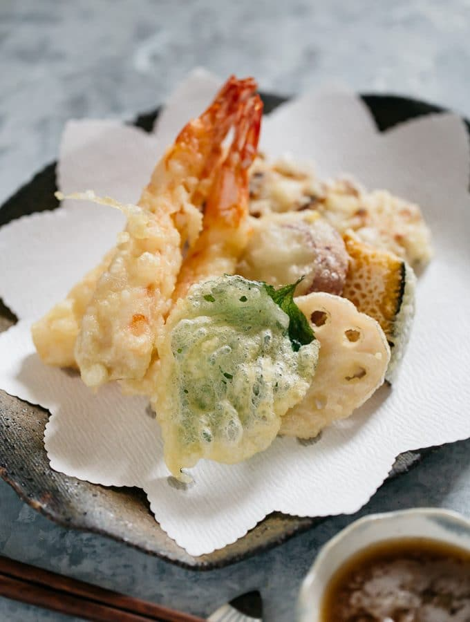 Two prawn tempura, shiso leaf tempura, renkon, kabocha and chikuwa fish cake tempura on a plate with a bowl of tentsuyu with gated daikon in it