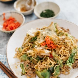 Yakisoba served on a round plate with little bowls of garnishes around it