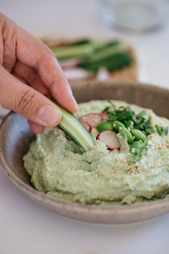 A hand with cucumber stick dipped in the bowl of edamame hummus