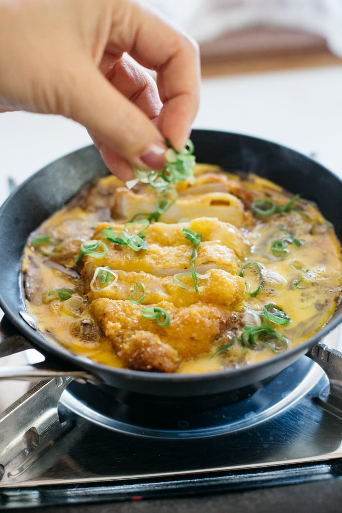 katsu being cooked in a frying pan with sauce and egg