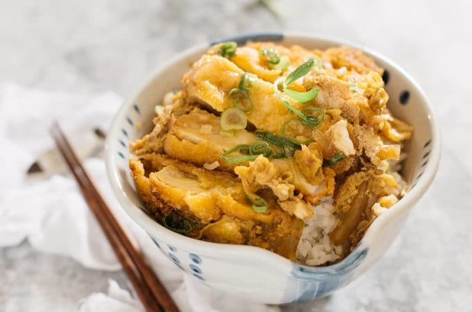 Katsudon served in a large Japanese rice bowl with a pair of chopsticks
