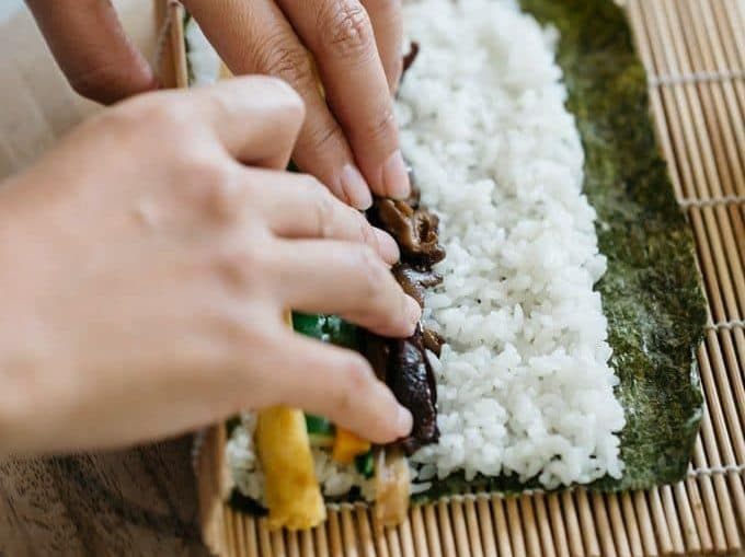 rolling a sushi with a bamboo sushi rolling mat
