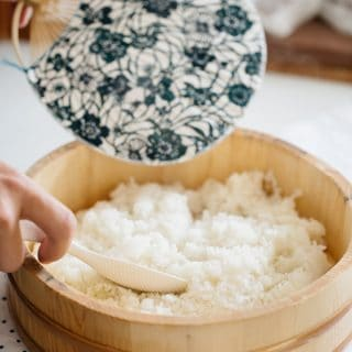 making sushi rice in a wooden tub with a Japanese fan Uchiwa