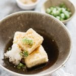Three Agedashi tofu pieces searved in a shallow bowl with grated daikon and broth