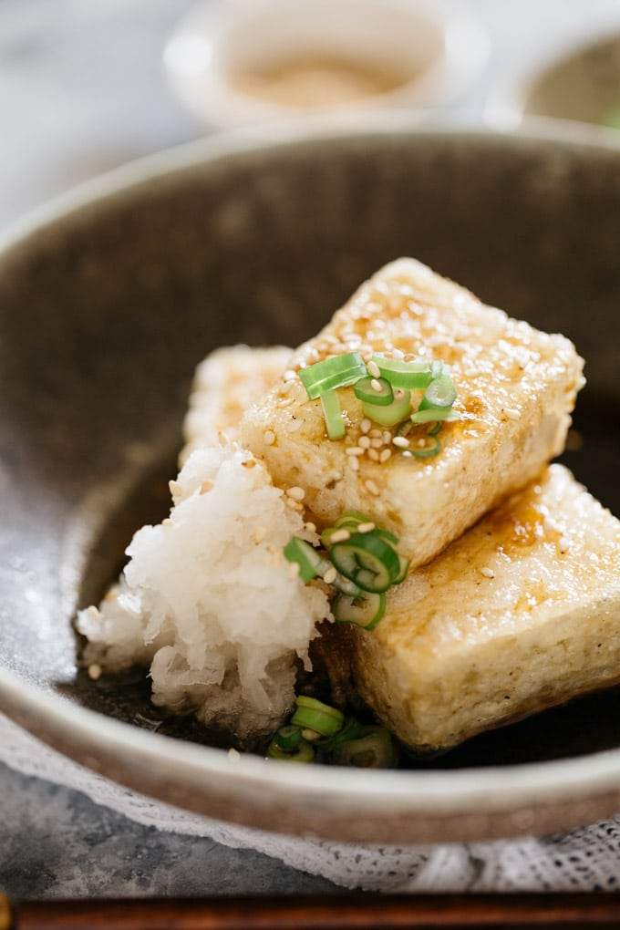 Three pieces of Agedashi tofu with broth in a Japanese pottery bowl