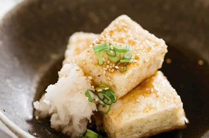 three pieces of Agedashi tofu served with grated daikon and broth