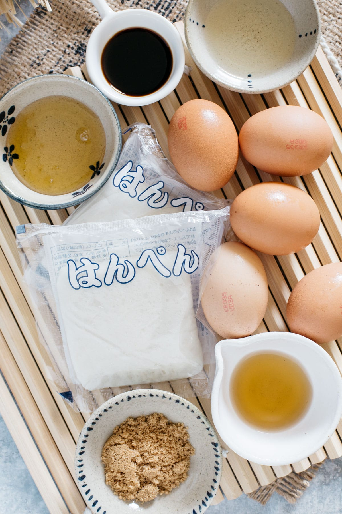 Japanese rolled omelette ingredients, 5 eggs, fish cakes, condiments on a bamboo mat