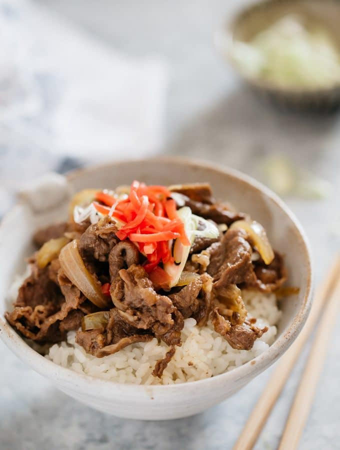 Gyudon served in a Japanese pottery bowl garnished with red pickled ginger on top