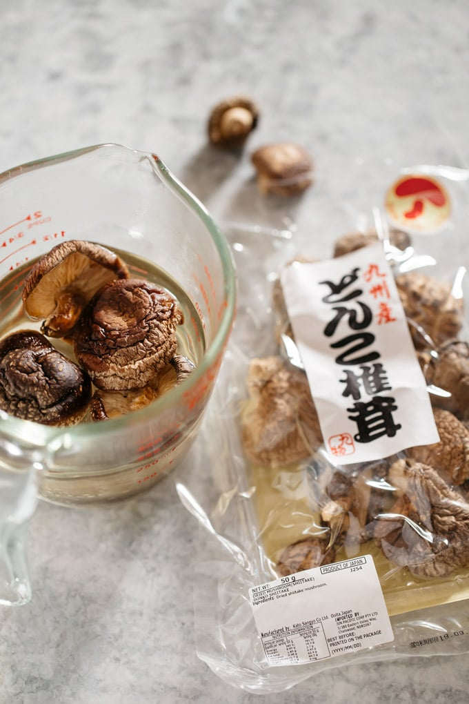 Dried shiitake mushrooms in a jug soaked in water and also in a packet.