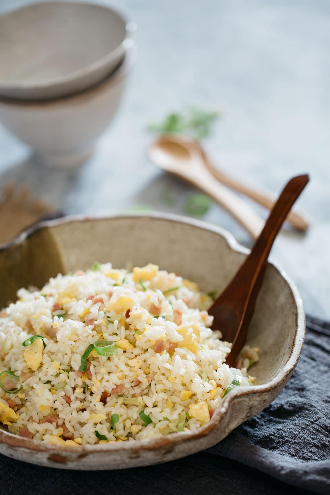 Japanese fried rice Yakimeshi is served in a big Japanese serving pottery with wooden serving spoon