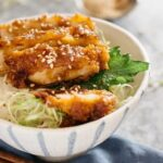 Miso Katsudon served in a Japanese pottery rice bowl with a pair of chopsticks
