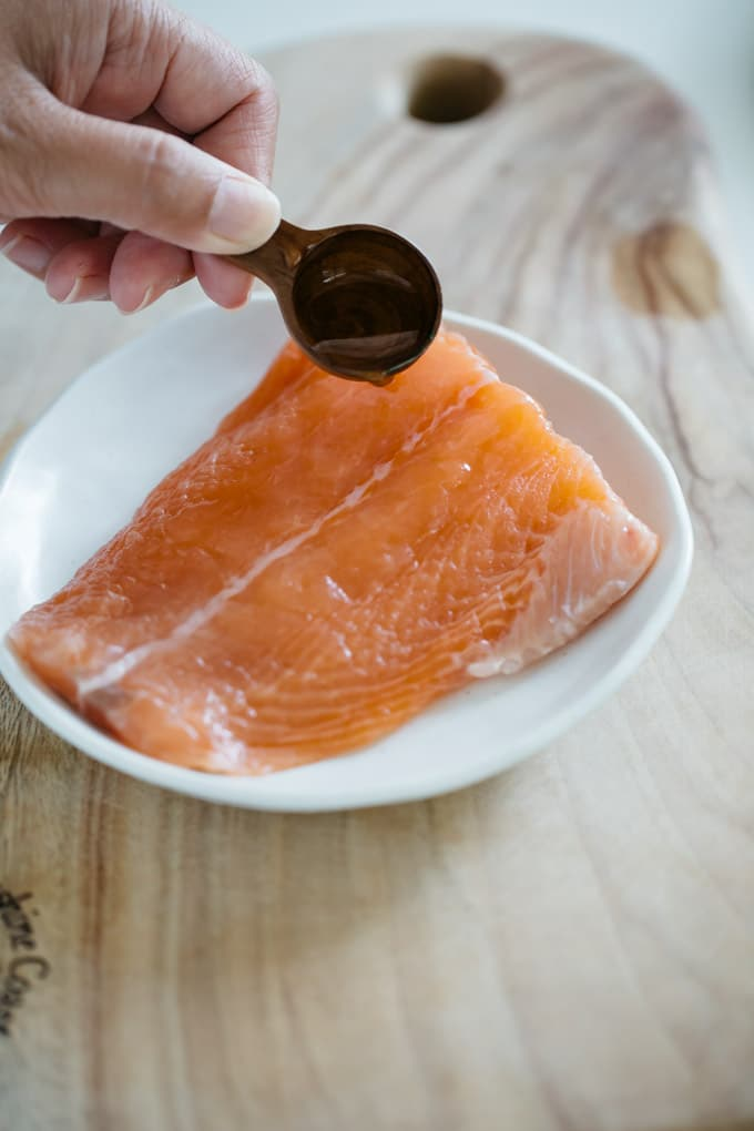 a hand sprinkling a tea spoon of sake over the salmon fillet