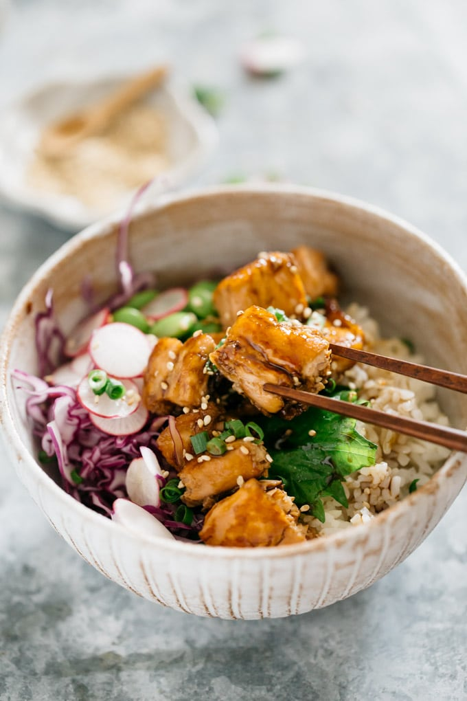 Teriyaki salmon bowls served in a bowl with a small bowl of sesame seeds