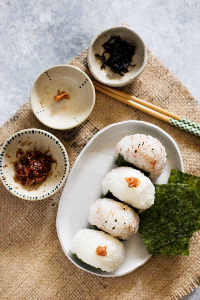 bird view of a white plate with Japanese rice balls and three small bowls