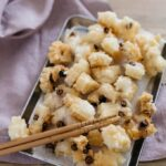 Japanese rice crackers Okaki just being cooked and cooling down on a rectangular tray.
