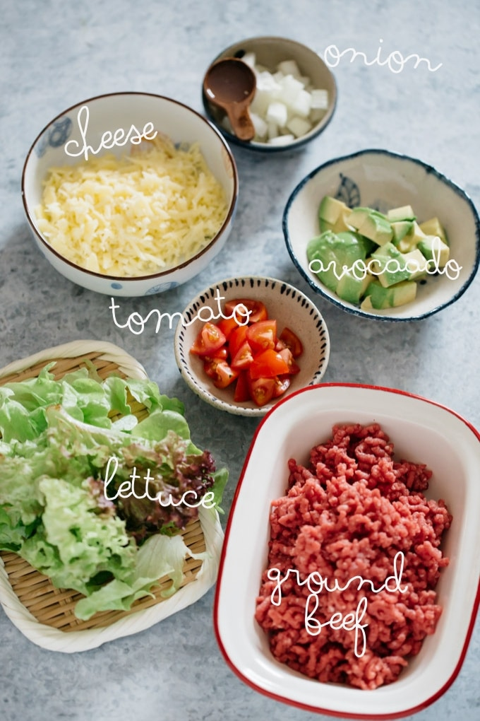 ingredients-ground beef, tomato, avocado chopped, lettuce grated cheese, chopped onion, and lemon juice on a table
