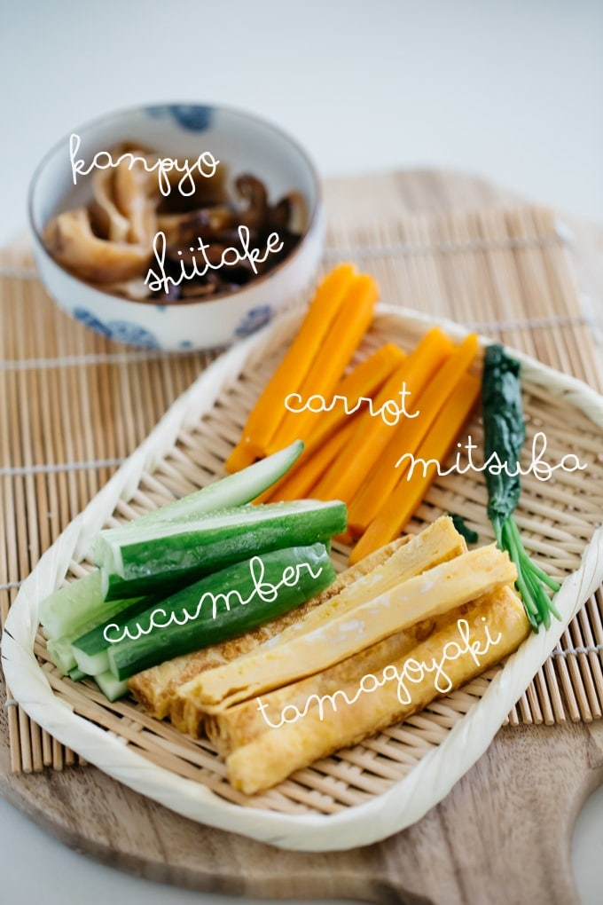 Futomaki sushi rolls ingredients on a bamboo tray - tamagoyaki, carrot, cucumber, mitsuba, and kanpyo
