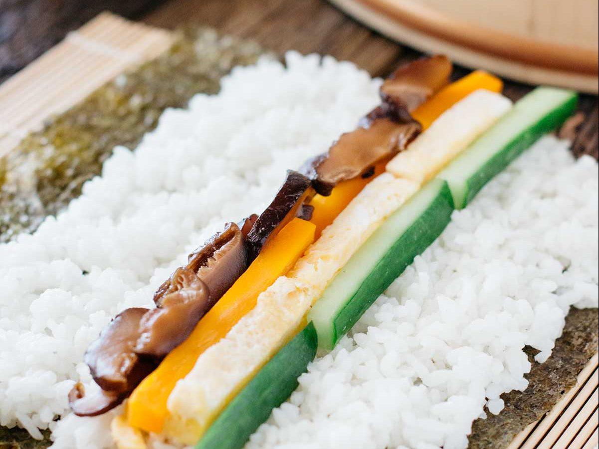 futo makizushi ingredients shiitake mushrooms, carrots tamagoyaki cucumber lined up on a sushi rice