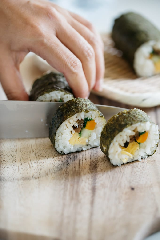 Cutting sushi rolls into small pieces