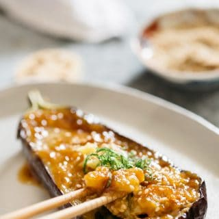 miso eggplant served on an oval shaped tray and a pair of chopstick digged into the eggplant