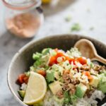 Okinawa Taco rice served in a shallow round bowl with lemon wedges in a background