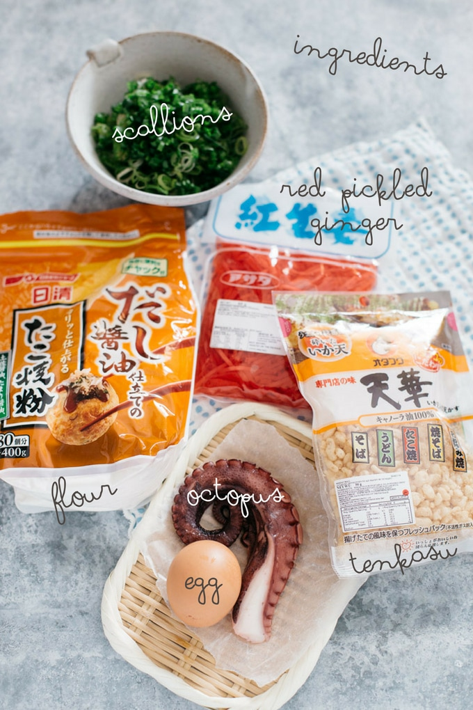 Takoyaki ingredients in original packets of flour, pickled ginger, tenkasu, chopped scallions in a bowl, cooked octopus and egg