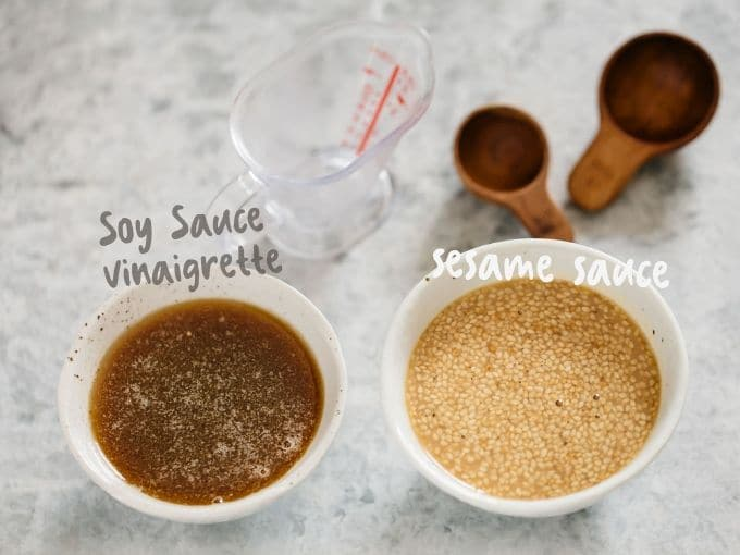 on the left, soy sauce vinaigrette in a small bowl. On the right, sesame sauce in a small bowl.