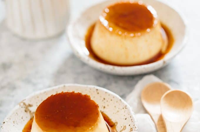 Two Japanese custard pudding served on two Japanese pottery plates with two wooden spoons