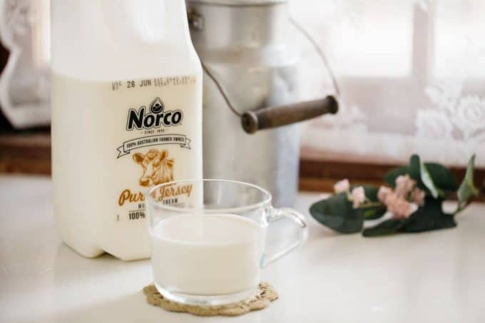 Norco brand milk bottle and a glass of milk on a kitchen bench