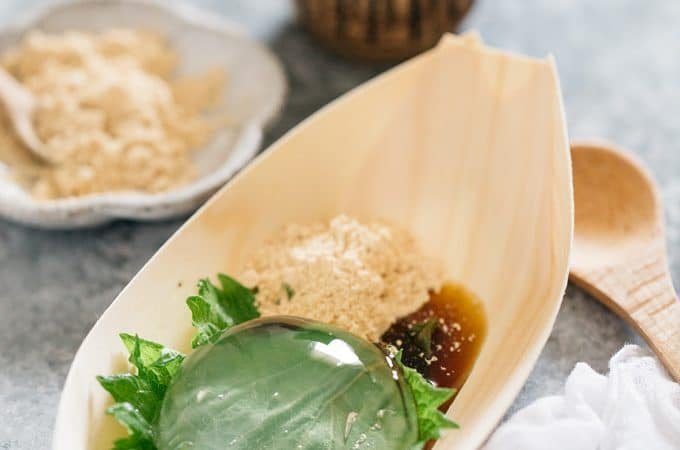raindrop cake served on a wooden boat shaped plate with kinko and kuromitsu