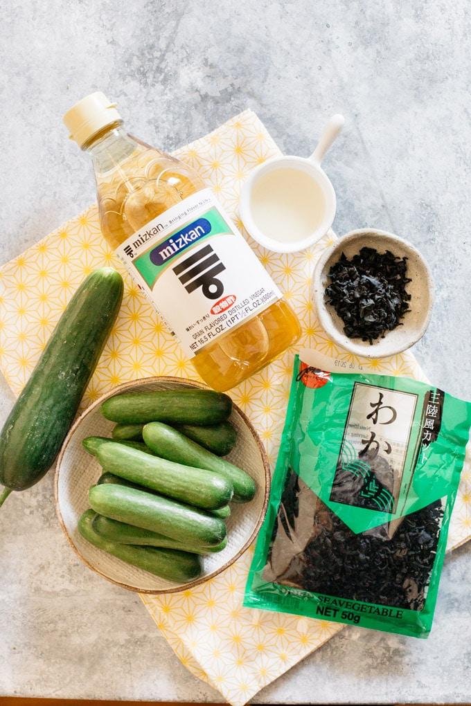 ingredients of Japanese cucumber salad displayed, cucumbers, a bottle of vinegar, dried wakame seaweed packet.
