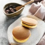 Two dorayaki on an oval shaped plate with a bowl of azuki bean paste