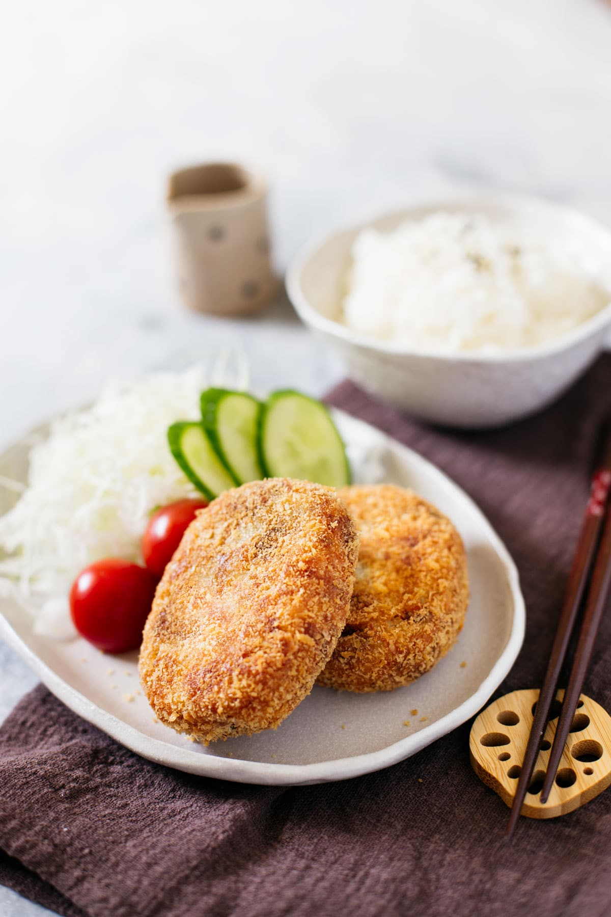 2 japanese potato croquettes served with shredded cabbage, cucumber and tomato on a oval plate