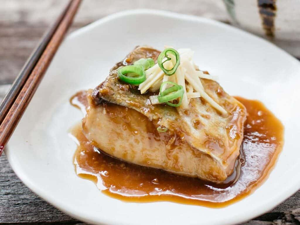 mackerel simmered in sweet miso, soy sauce and mirin sesrved on a white plate with finely chopped ginger