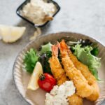 Three fried shrimp with tartar sauce on a round plate with green salad leaves, tomato and a wedge of lemon